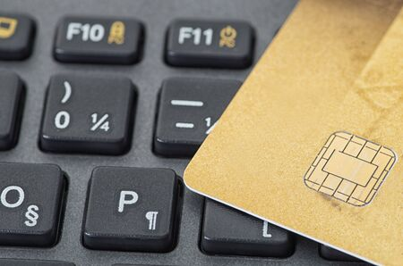 Golden credit card on black keyboard closeup studio shot 版權商用圖片