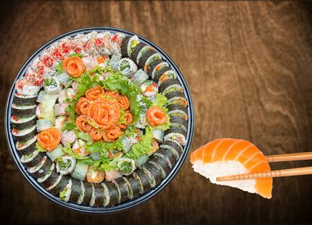 Variety of sushi rolls and sashimi on a plastic platter against wooden background Stock Photo