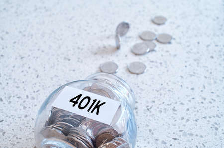 accrue: 401k retiring plan concept with a glass jar full of coins on a marble counter top