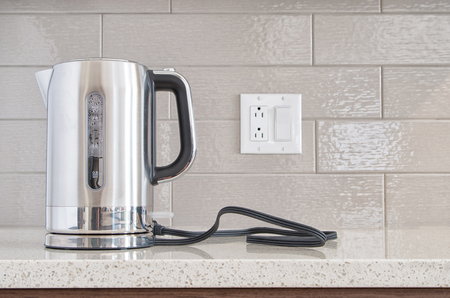 Modern electric stainless steel kettle sitting on its base on a granite counter top against a ceramic background