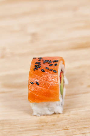Piece salmon sushi on wooden plate
