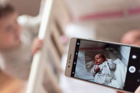 Mother pictures her newborn son while lying in her bed