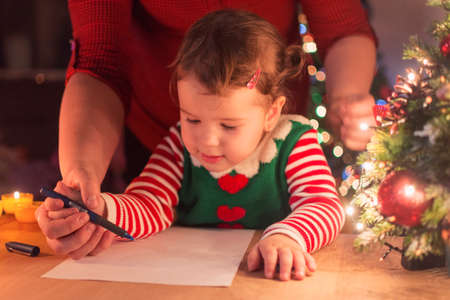 A cute little girl writes on her paper her wishes that she will send in a letter to Santa Claus Reklamní fotografie
