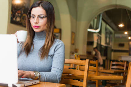 The young pub owner works on a laptop computer Stock Photo