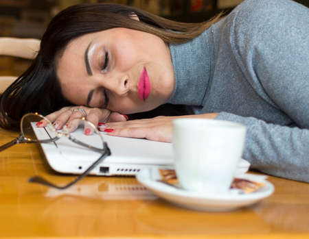 a very tired business woman sleeping on a laptop computer