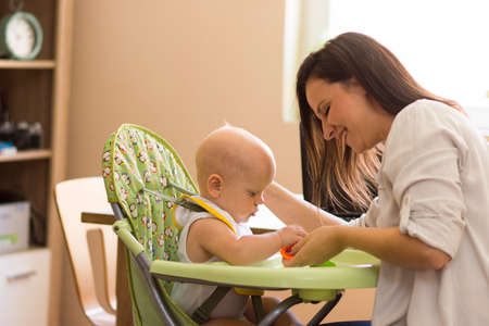 The mother and the baby are having fun while sitting in their home. The mother animates the baby sitting in her baby chair. Motherhood is a very hard and responsible job. Banco de Imagens