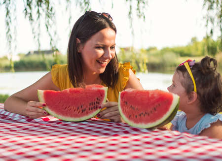 A single mother and his daughter sit at the table and eating watermelon slice. The female part of the family at the picnic near the canal in nature. The love between mother and daughter.