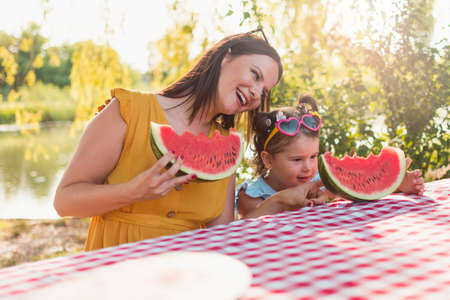 A single mother and his daughter sit at the table and eating watermelon slice. The female part of the family at the picnic near the river in nature. The love between mother and daughter.