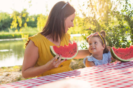 A daughter and mother sit at the table and eating watermelon slice. Girls sit at the table and enjoying the sweet fruit.. Fruit consuming.