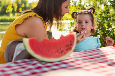 A daughter and mother sit at the table and eating watermelon slice. Girls sit at the table and eating watermelon slice. A mother cleaning daughter with the napkin after sweet fruit. Fruit consuming.