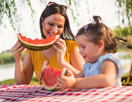 Mother and daughter enjoying a watermelon slice in the park near the river. Mother and daughter enjoying fruit while spending time together outdoor. Front view.