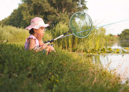 Sweet little girl sitting on the grass and patiently fishing near the river. Little girl, 4-5 years, spending fishing time alone on the river coast. Kids and fishing concept. 写真素材