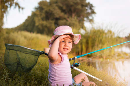 Sweet little girl sitting on the grass and catching the fish near  the river. Little girl, 4-5 years, spending fishing time alone on the river coast. Kids and fishing. 写真素材