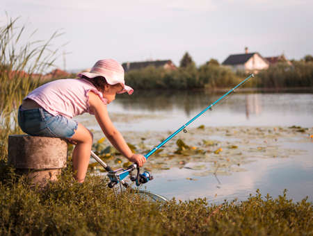 Sweet little girl on fishing near the river. Little girl, 4-5 years, spending fishing time alone on the river coast. Kids and fishing. Rear view. 写真素材