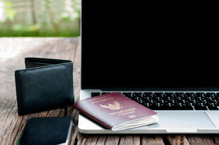 blank screen: Open laptop with digital smartphone wallet and passport isolated on old wooden desk outdoor.