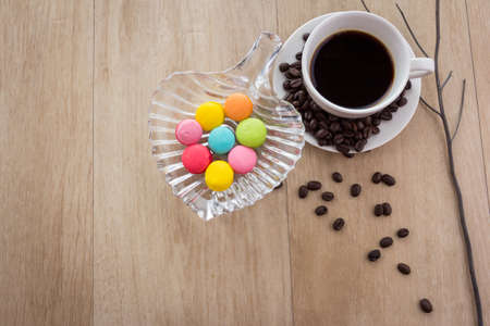 good color: cup of espresso coffee with colourful French macarons on wooden background