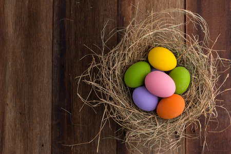 Easter eggs in nest on old wooden background