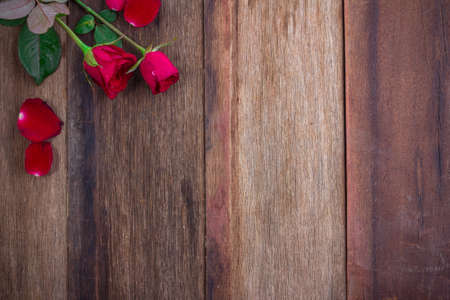 wedding gifts: red roses on wooden background