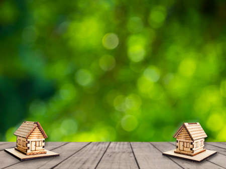miniature wooden house on wooden mock up over blurred green garden on day noon light. Image for property real estate investment concept. Stock Photo