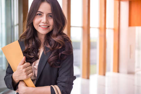 Beautiful Asia business woman over blue office background.
