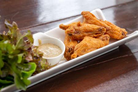 Fried Chicken, Sauce und Bio-Gemüse, wunderschön dekoriert in weißem Teller.