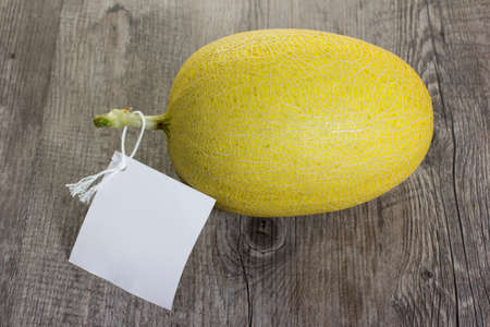 Orange melon on wood table with white lable.