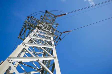 High voltage pole on blue sky background.