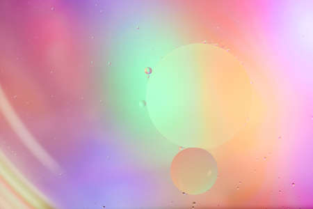 Top view movement of oil bubbles in the liquid. Oil surface multicolored background. Fantastic structure of colorful bubbles. Colorful artistic image of oil drop floating on the water