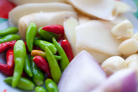 Young ginger, chillies, garlic and onions on a plate.