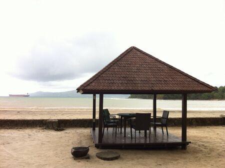Cabana by the beach amidst cloudy sky Stock Photo