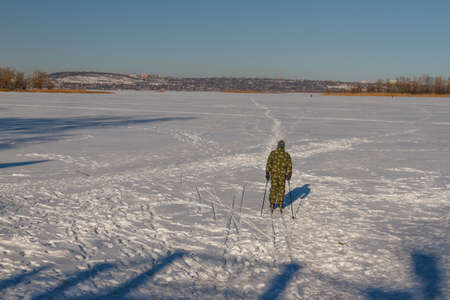 water skiers: Bright frosty winter day. Frozen River Volga. Man skiing.