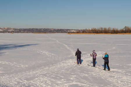 water skiers: Bright frosty winter day. Frozen River Volga. Group of people skiing. Stock Photo