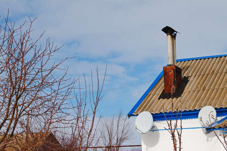 A satellite dish on the roof of an old house in the village