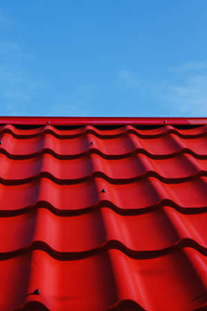 Red roof from a metal tile on a blue sky background