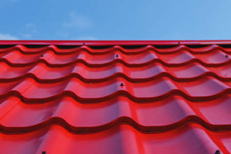 Red roof from a metal tile on a blue sky background Stock Photo