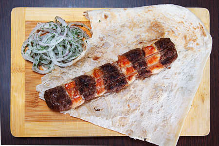 Kebab of minced meat on wooden board with vegetables. close-up Stock Photo