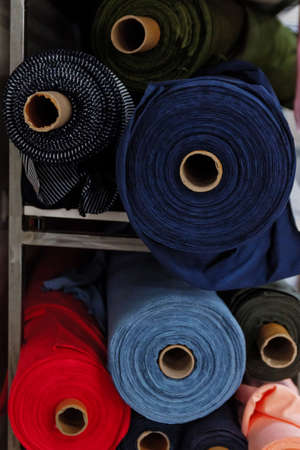 Rolls of fabric and textiles in a factory shop.