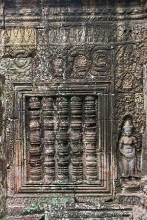 Khmer devata guardian shown in stone in Ta Prohm temple, in Angkor, Siem Reap, Cambodia. Фото со стока