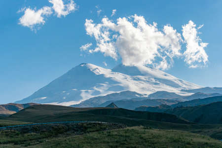 Scenic view of the highest peak in Europe, mount Elbrus with green hills on a Sunny summer day.