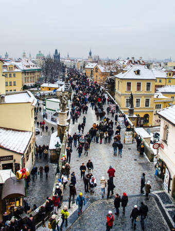 PRAGUE, CZECH REPUBLIC, JANUARY 30, 2015: people are walking from the charles bridge towards prague castle in prague, whose rooftops are covered by snow.