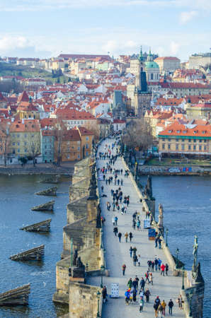 st charles: people are trying to cross charles bridge in prague in order to get to the famous prague castle, hradcany district and church of saint nicolas which are situated on the opposite shore of vltava  moldau river.