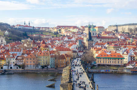 saint nicolas: people are trying to cross charles bridge in prague in order to get to the famous prague castle, hradcany district and church of saint nicolas which are situated on the opposite shore of vltava  moldau river.