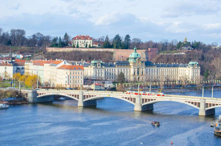 manes: view of the manes bridge with a building of the czech parliament behind it.