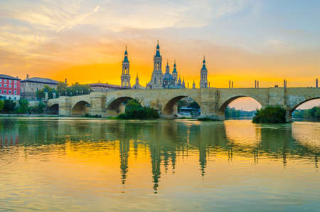 sunset view of the basilica de nuestra senora de pilar and puente de piedra in Zaragoza, Spain  写真素材