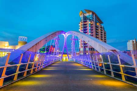 Vista de una pasarela iluminada en los muelles de Salford durante la noche en Manchester, Inglaterra