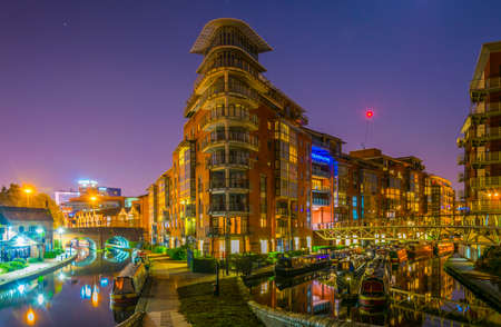 Night view of brick buildings alongside a water channel in the central Birmingham, England