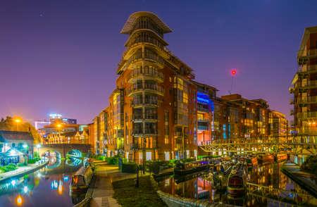Vista nocturna de edificios de ladrillo junto a un canal de agua en el centro de Birmingham, Inglaterra