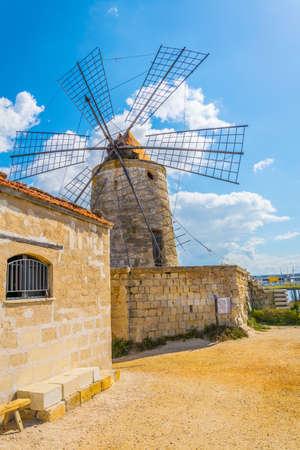 View of a windmill in the Saline di Trapani e Paceco natural reserve near Trapani, Sicily, Italy Archivio Fotografico