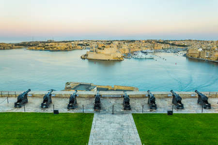 Sunset view of the Saluting Battery facing Birgu town with Fort st. Angelo and Senglea in Valletta, Malta Imagens