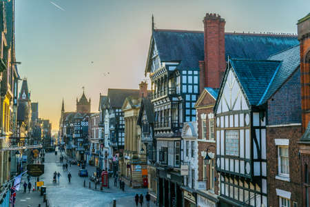 CHESTER, UNITED KINGDOM, APRIL 7, 2017: Traditional tudor houses alongside the Eastgate street in the central Chester during sunset, England